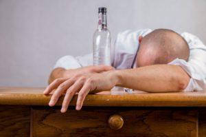 お酒を飲みすぎて二日酔いでうなだれる男性
