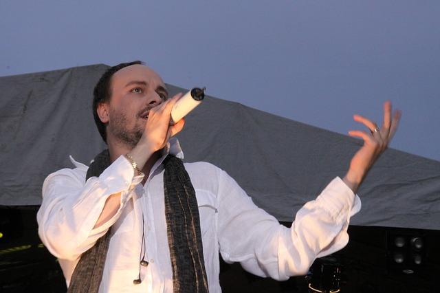 手を挙げて歌う男性